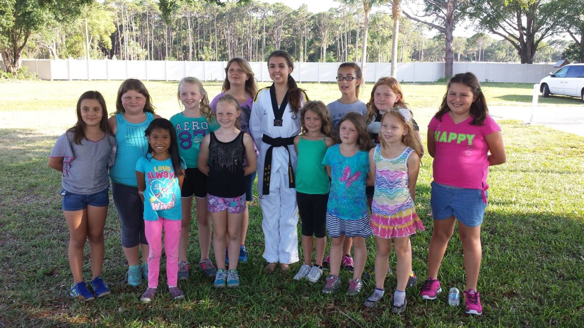 A girl in a karate outfit surrounded by a group of younger girls
