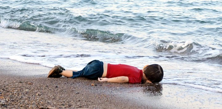 A picture of a drowned syrian refugee child on the shore of a beach