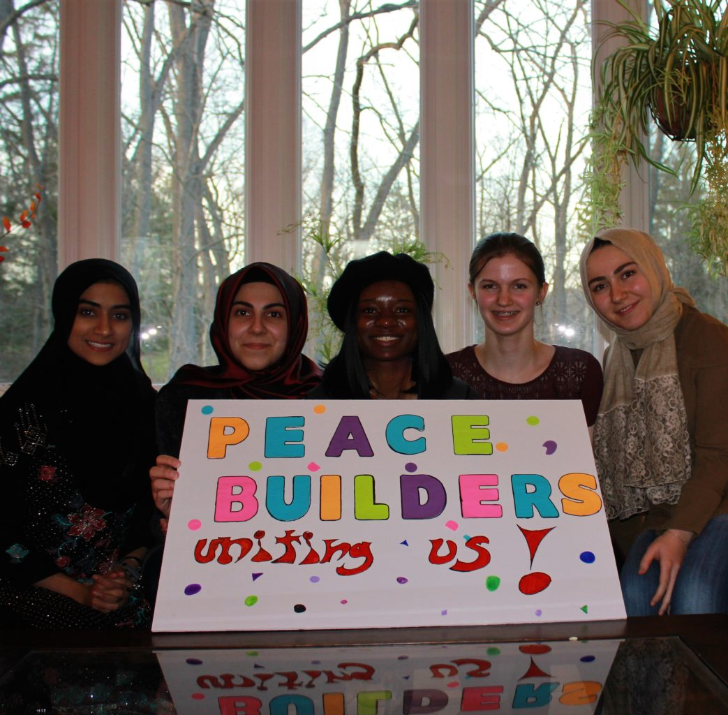 "A group of young people with a sign that reads ""peace-builders, uniting us!"""