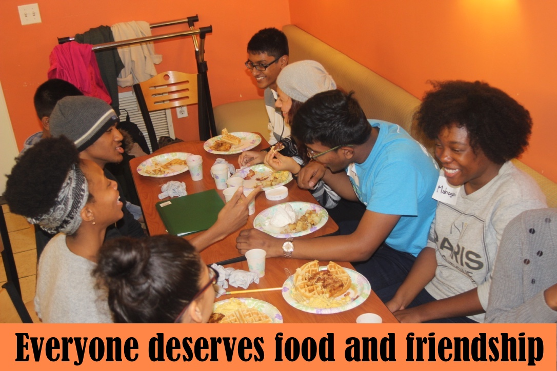 "Young people around a table eating and text that reads ""everyone deserves food and friendship"""