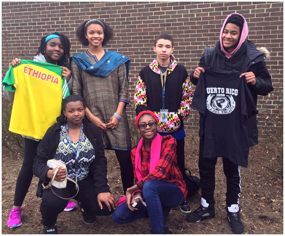 A group of young people wearing or holding clothes that represent their cultures