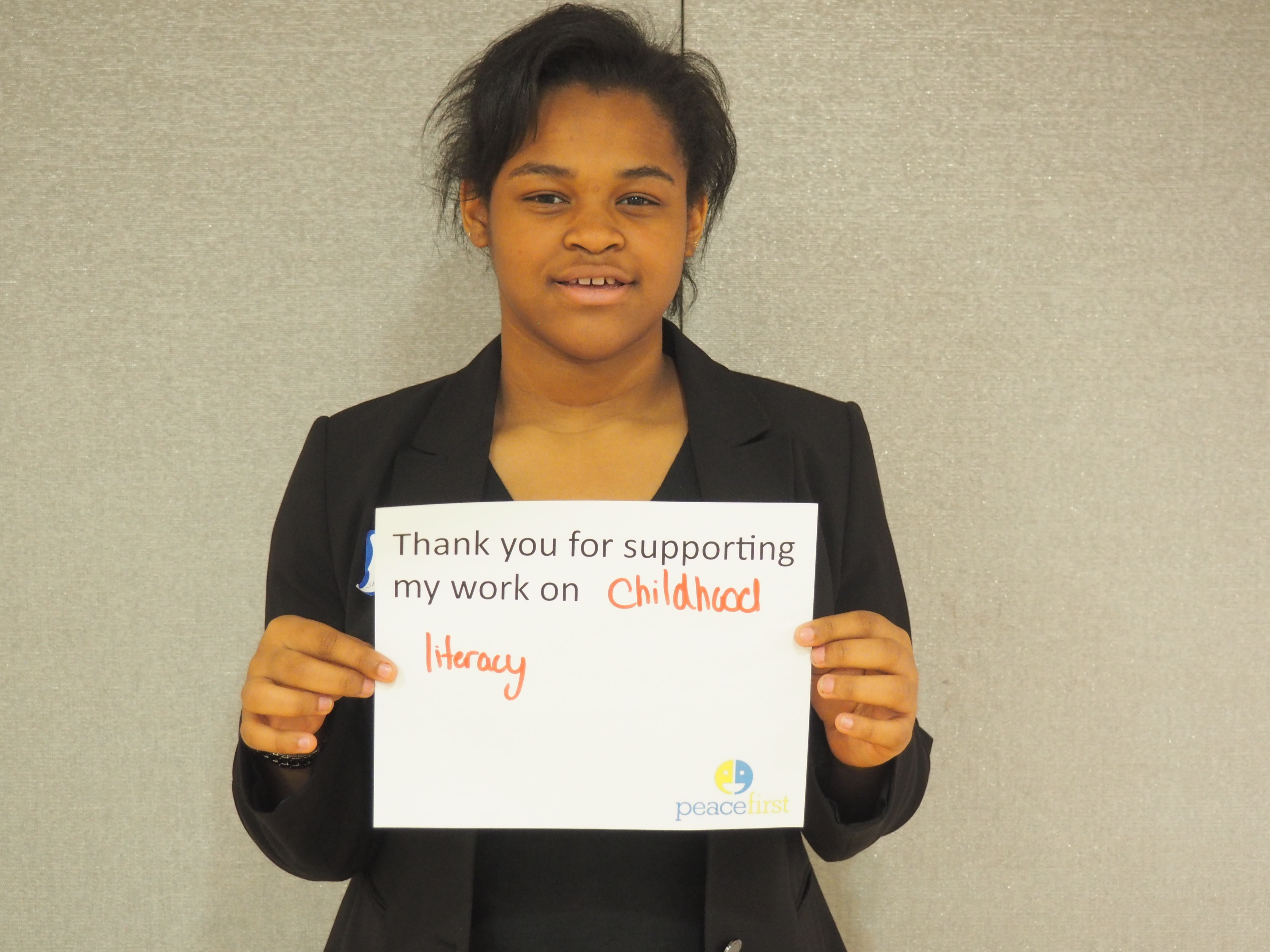 Imani holding a sign to explain the importance of childhood literacy.