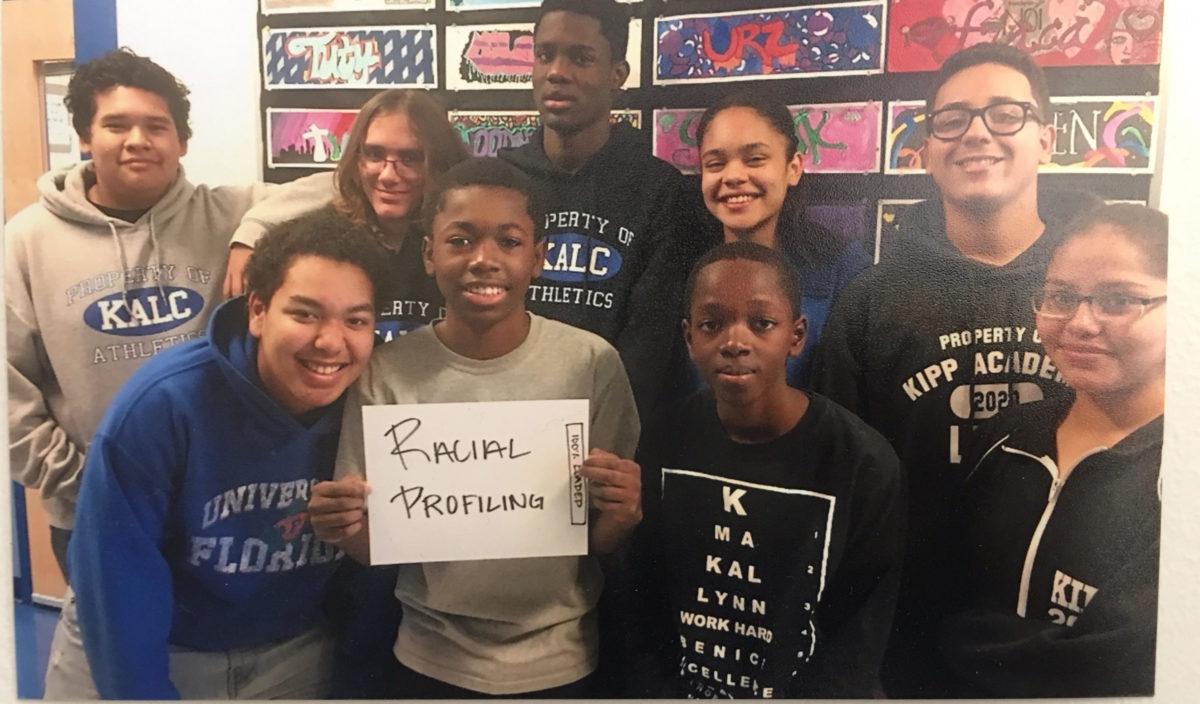 "A group of young people holding a sign that reads ""racial profiling"""