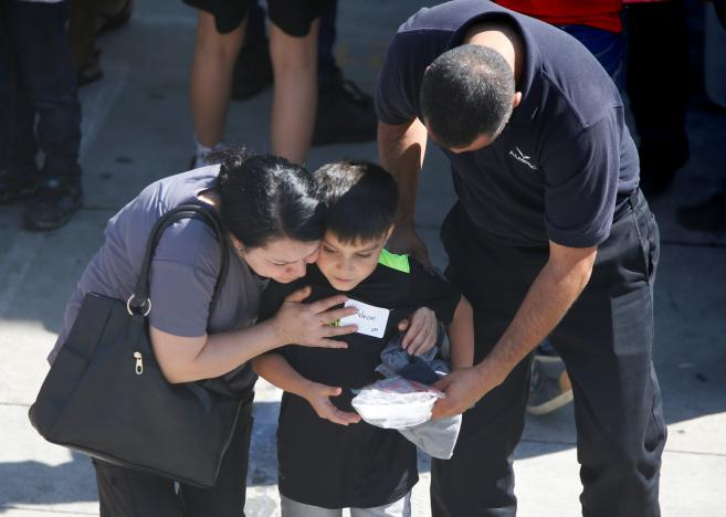 A student who was evacuated after a shooting at North Park Elementary School is embraced after groups of them were reunited with parents waiting at a high school in San Bernardino, CA. PHOTO CREDITS: Reuters/Mario Anzuoni