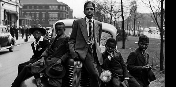 An old photograph of five boys sitting on a car