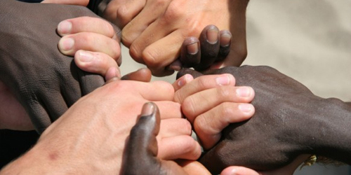 A group of different colored hands holding each other