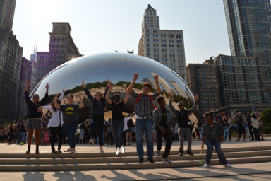 Young people jumping in front of the Chicago bean