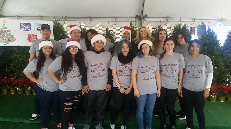 A group of young people wearing santa hats