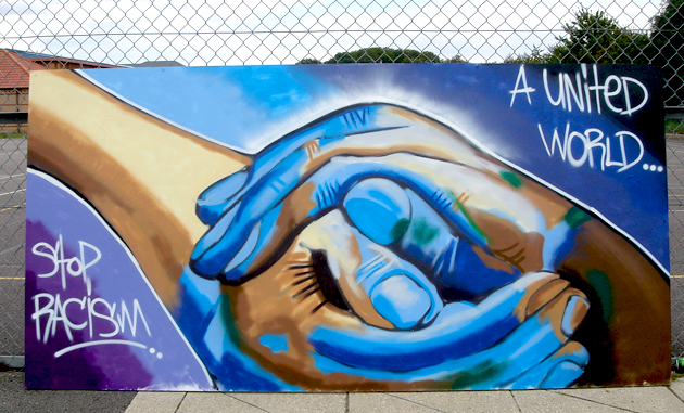 "A mural of people holding hands that reads ""a united world, stop racism"""