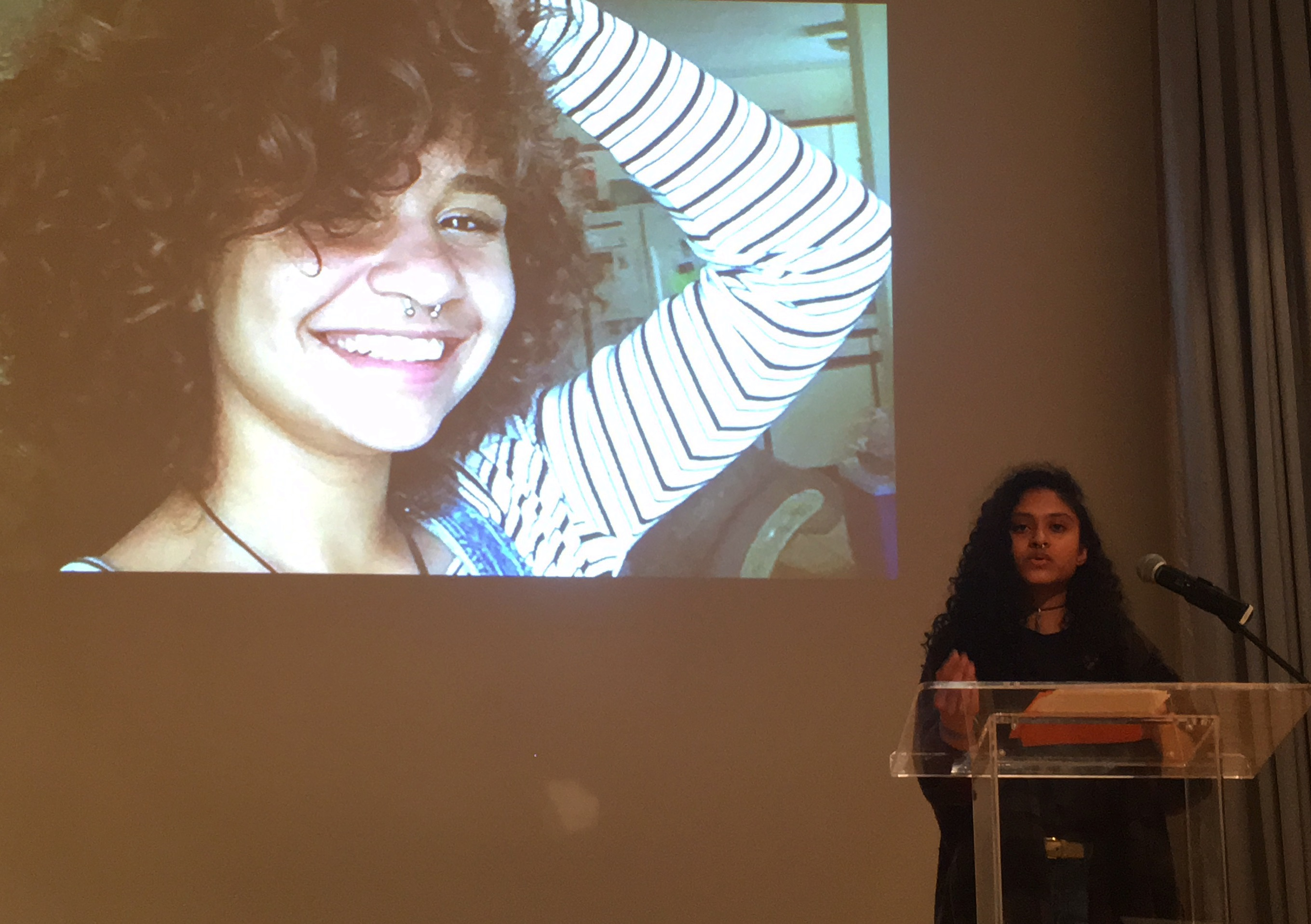 This is a photo of Fatima Dizon, creator of Harlem Lighthouse, purposing her project at The New Museum in 2017. There is a large photo of Maylin Reynoso behind her. Maylin Reynoso was a young woman of color who went missing in 2016 and was found dead later that year. Harlem Lighthouse was created in Maylin's legacy.