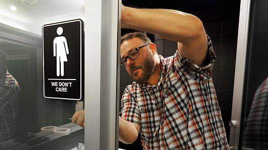 Museum manager Jeff Bell adheres informative backing to gender-neutral signs in the 21C Museum Hotel public restrooms on May 10, 2016, in Durham, North Carolina. PHOTO CREDITS: Getty Images via CNBC