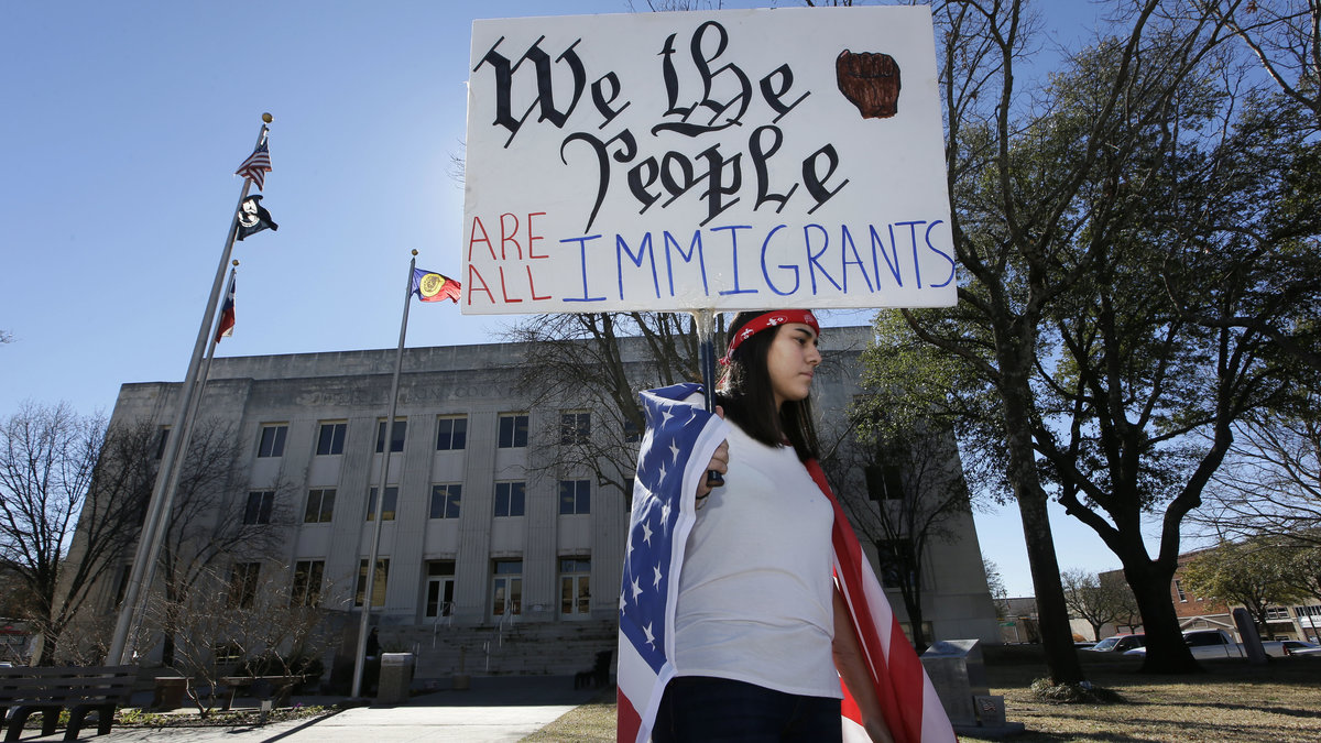 Observing a Day Without Immigrants, high school senior Vicky Sosa holds a sign outside the Grayson County courthouse in Sherman, TX. PHOTO CREDITS: NPR via LM Otero/AP