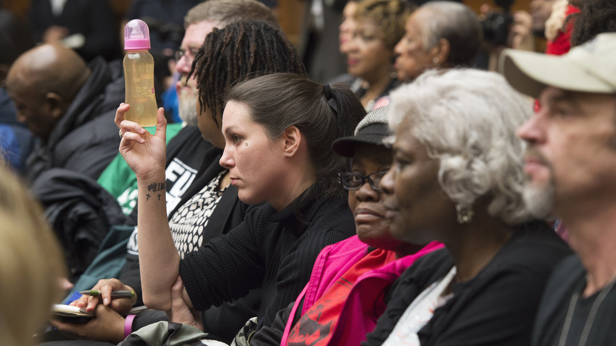 Jessica Owens holds up a baby bottle of water from her home in Flint, Mich., while attending a hearing on Capitol Hill about Flint's water crisis. PHOTO CREDITS: Molly Riley/AP via NPR