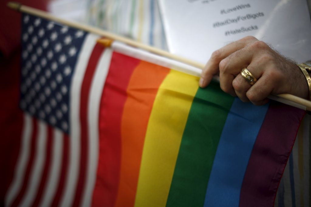 A married gay man carries the rainbow and U.S. flags at a celebration rally in West Hollywood, California, following the 2015 Supreme Court decision on marriage equality. PHOTO CREDITS: Reuters/Nicholson